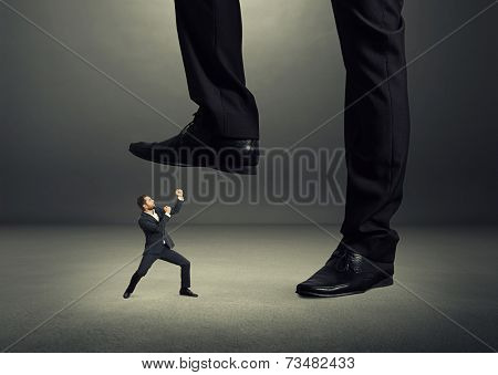 concept photo of conflict between subordinate and boss. angry young businessman showing fist and looking up at big boss. photo in the dark room poster