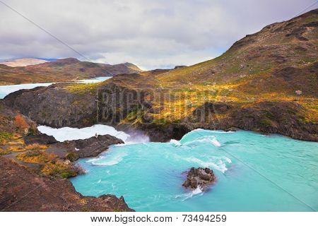 Gorgeous National Park in Chilean Patagonia. Affluent bustling Salto Grande waterfall with emerald water. On the edge of the cliff stands woman- tourist