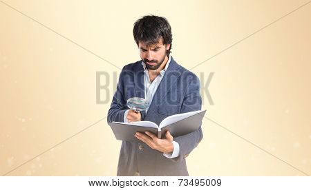 Businessman With Loupe Reding A Book Over Ocher Background
