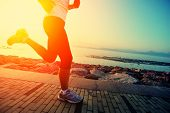 Runner athlete running at seaside. woman fitness silhouette sunrise jogging workout wellness concept. poster
