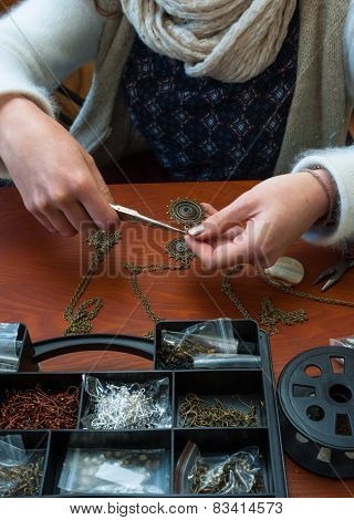 woman making craft jewelry