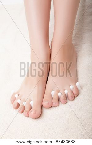foot pedicure applying woman's feet in toe separators