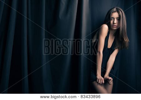 Sexual fashion model posing in front of stage curtains.