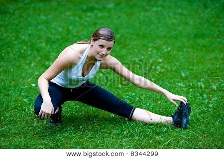 Cute young girl stretshes leg on green grass