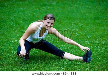 hübsch junges Mädchen Stretshes Bein auf grünem Gras