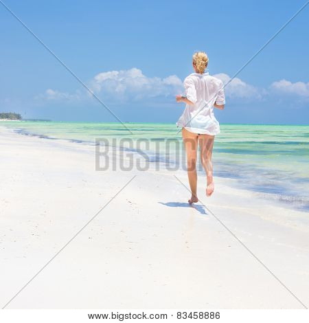 Woman running on the beach in white shirt.