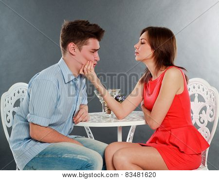 Girl With Her Drunk And Sad Boyfriend At Table, In Studio Isolated On Gray