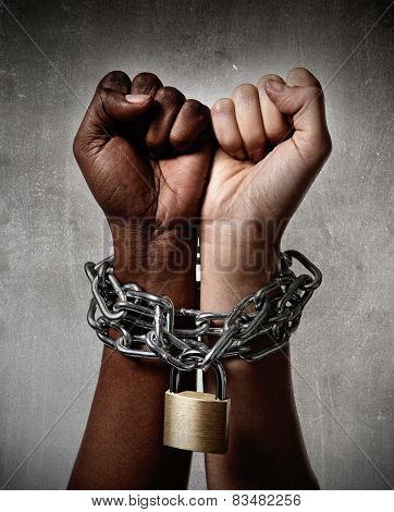 white Caucasian hand chained with iron chain and locked together with black ethnicity female around wrists in togetherness multiracial respect and understanding concept poster