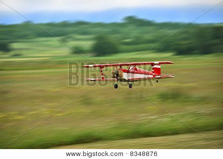 Red and white radio controlled aircraft with methanol engine flying over grassy field. The image shows motion blur. poster