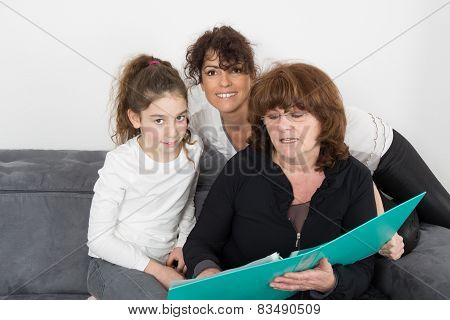 A cheerful grandmother with her daughter and her grand daughter Indoors
