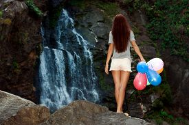 The woman with balloons on the background of the waterfall
