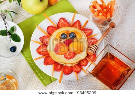 Children's breakfast pancakes smiling face of the sun lion strawberry blueberry and apricot, cute fo