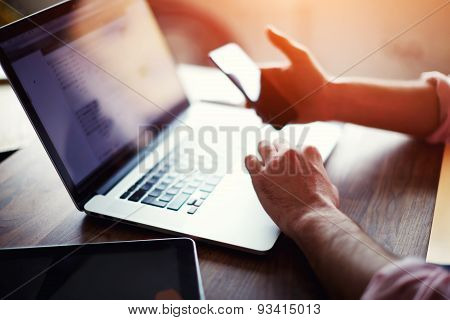 Rear view of business man hands busy using cell phone at office desk while browsing web sites