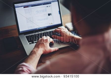 Cropped image of a young male student texting on computer sitting at wooden table