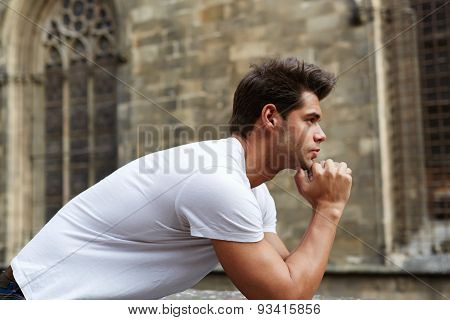 Pensive young man standing against gothic building while thinking about his choice