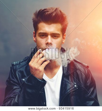 Square size portrait of handsome man exhaling cigarette smoke looking to the camera