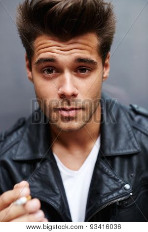 Close up portrait of handsome masculine model smoking cigarette and exhaling the fume