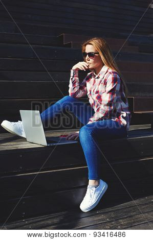 Charming girl in glasses using laptop while sitting on wooden stairs in the sun