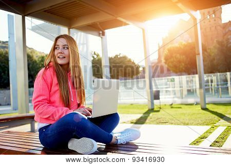 Portrait of a young girl sitting with open white laptop on a bench outdoors and looks aside