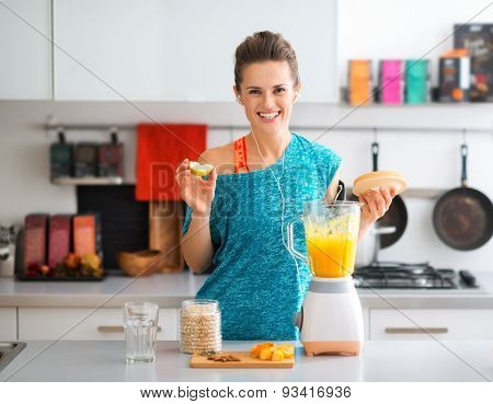 Happy, Fit Woman In The Kitchen Preparing A Healthy Smoothie
