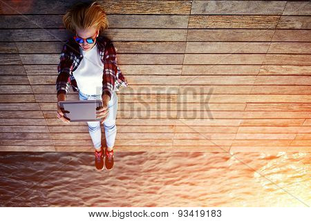 Portrait of young stylish girl is lying on a wooden pier taking self portrait on the touch tablet