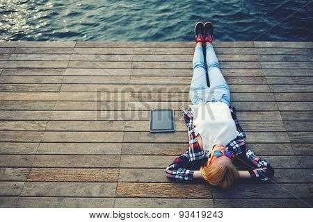 Active tourist lying on the wooden pier after a long walk and enjoy the sun and the noise of the sea