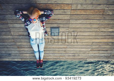 Portrait of a young tourist lying on a wooden pier standing beside her tablet and enjoys the sun