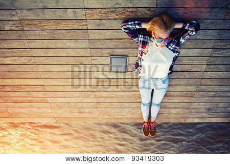 Portrait of a young beautiful girl lying on a wooden pier and enjoys good weather and sea