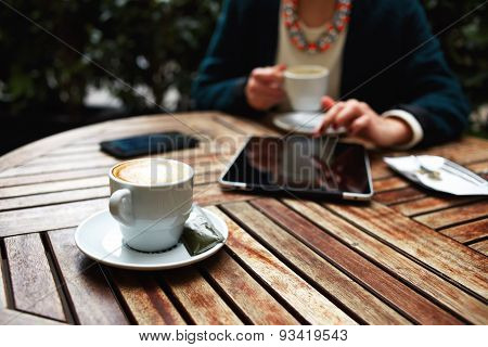 Successful business lady sitting on a wooden table in a cafe on which stands its tablet and phone