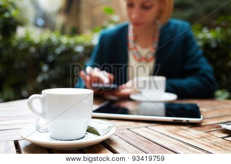 Elegant young woman working on a touch screen phone sitting in a cafe with a cup of coffee.