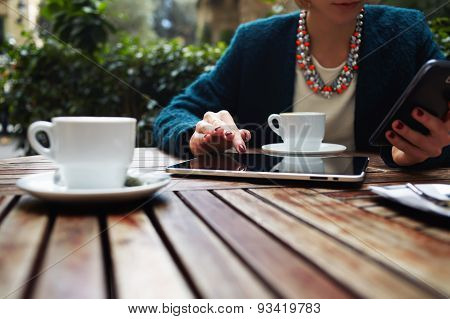Girl freelance typing on the phone and working on touch screen tablet sitting in cafe
