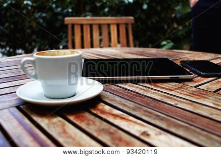 Digital tablet smart phone and and coffee mug on a wooden table with empty chair black touch screen