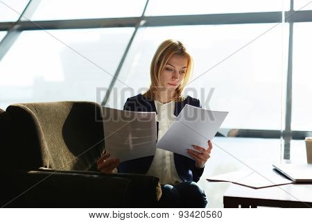 Portrait of a young successful business lady working on documents sitting in a large light office