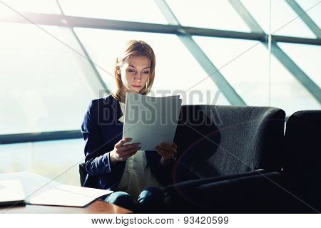Portrait of a young business lady sitting by their computers and read documents in a large office