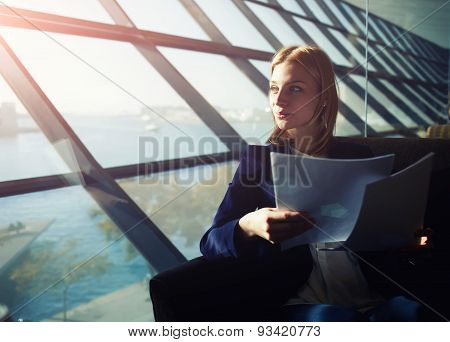 Portrait of a young successful business woman sitting in a big office with documents in hand.