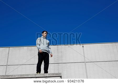 Portrait of a young parkour athlete standing on the roof of a large building and is preparing to jum
