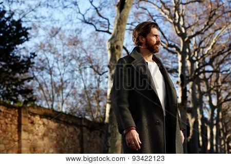 Portrait of well dressed man with beard posing outdoors looking away confident and focused.