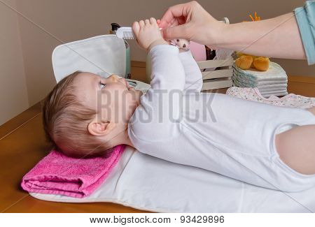 Hand of mother combing her baby lying