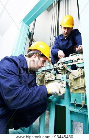 two male technician machinist worker at work adjusting elevator mechanism of lift with spanner poster