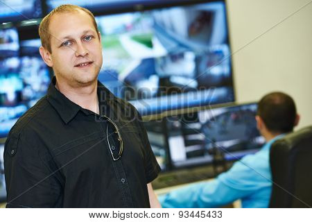 security executive chief in front of video monitoring surveillance security system poster