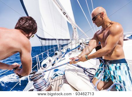 Two handsome shirtless sailors working on sailboat, pulling rope on crank, summer time activity, spending vacation in a sea traveling
