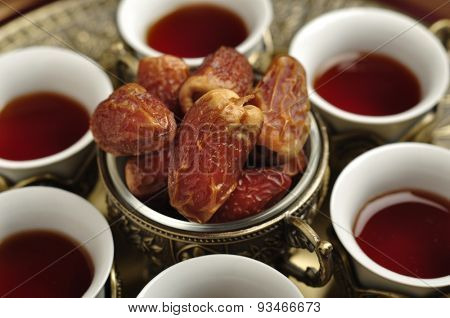Set of Arabic tea cups with date fruits. Close up.