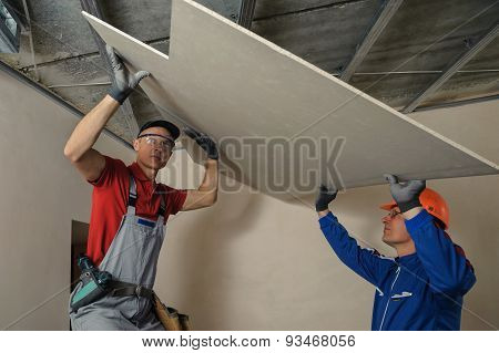 Drywall Installers. Men holding a gypsum board figured cut poster