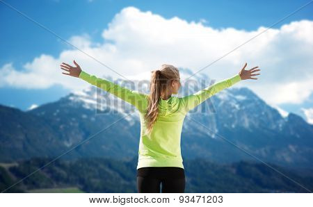 fitness, sport, peope and emotions concept - happy woman in sportswear enjoying sun and freedom over mountains and blue sky background from back