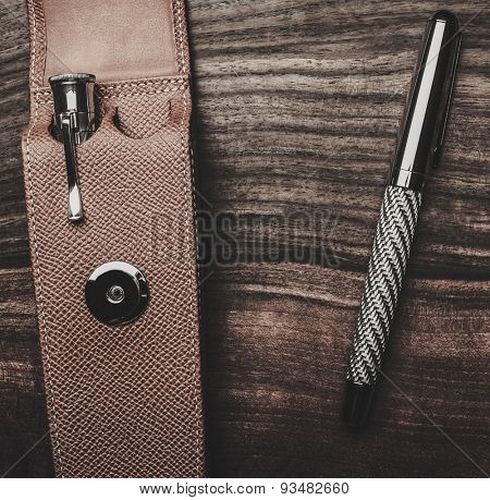 Luxurious rollerball pen on a wooden background