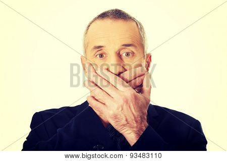 Embarassed businessman covering mouth with hands.