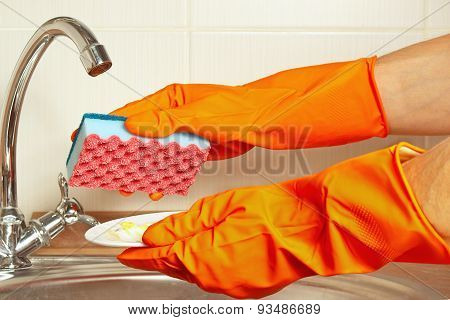 Hands in gloves with sponge and dirty plate over the sink in kitchen