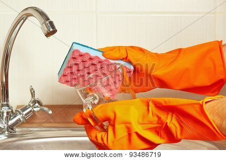 Hands in rubber gloves with sponge and dirty glass over the sink in kitchen