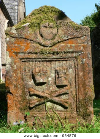 an odd looking moss covered gravestone in a churchyard in luss scotland - decorated with skull and crossed bones poster