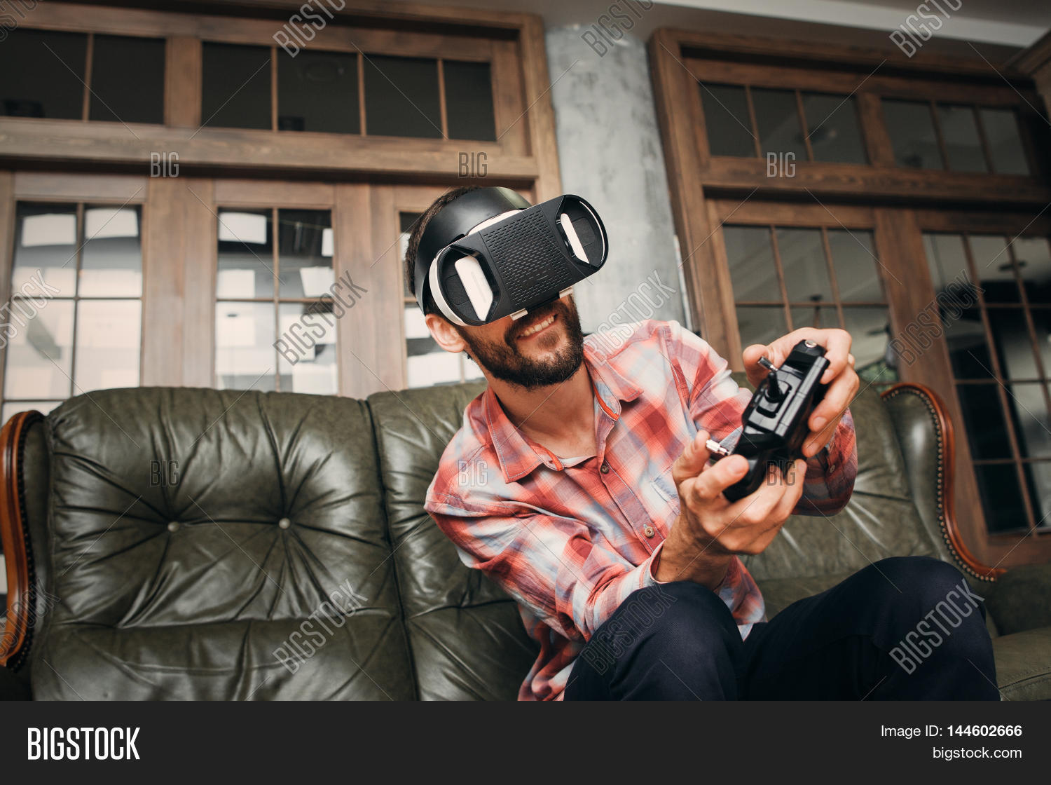 0b2bc0afeabe Young man playing video games in virtual reality headset. Male adult with  joystick and vr